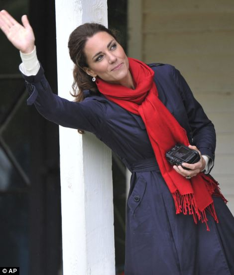 Camera in hand, Kate waves to her husband as he takes part in the helicopter demonstration