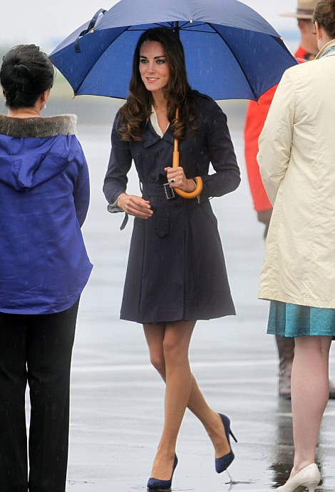 Brolly holiday: Catherine receives flowers as she and Prince William arrive in Yellowknife