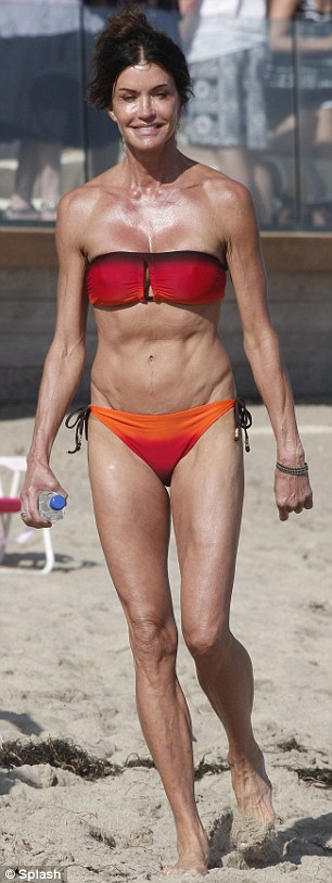 Ripped: Janice Dickinson showed off her incredibly muscular figure in a very tiny bandeau bikini today as she celebrated Fourth Of July on Malibu beach