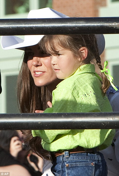 Kate, the Duchess of Cambridge, speaks to a little girl at the Calgary Stampede on Thursday,