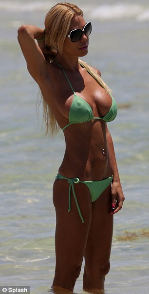Strike a pose: The former Playmate showed off her deep tan as she hit surf
