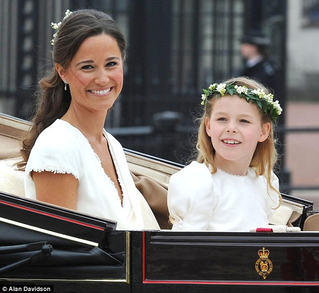 Pretty: Pippa rides in the carriage from Westminster Abbey towards Buckingham Palace with bridesmaid Margarita Armstrong-Jones on her sister's wedding day