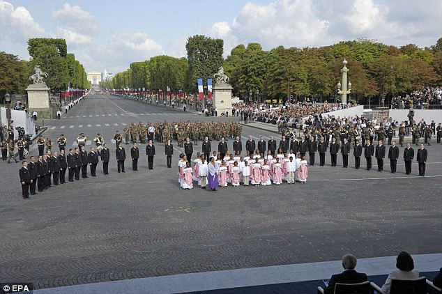 A chorus from the French territories sings during the Bastille Day parade. This year the French troops deployed overseas and firemen are being honoured