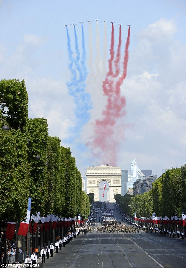 French air force Alpha Jets (Patrouille de France) paint the French Tricolour in the sky with smoke as they fly over the Arc de Triomphe