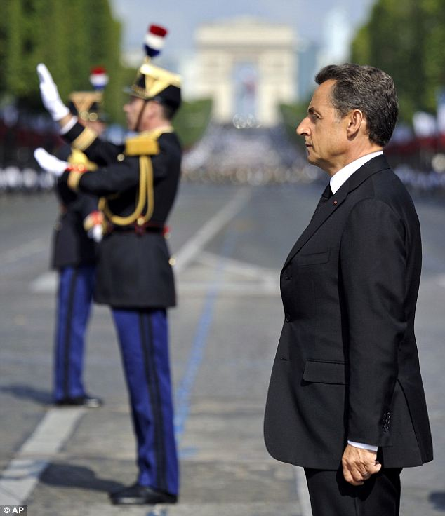 French President Nicolas Sarkozy listens to the Republican Guards 1st infantry regiment military band before the parade