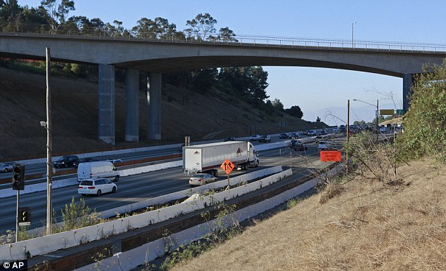 Closure: Traffic flows relatively freely last Sunday on Interstate 405 beneath the Mulholland Drive bridge in Los Angeles near sunset - but that will change when 10 miles of the vital artery is closed this weekend