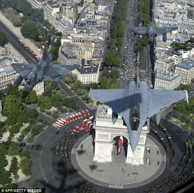 A French Rafale jet flies over the Arc de Triomphe flanked by two Mirage 2000-N today during the Bastille Day military parade