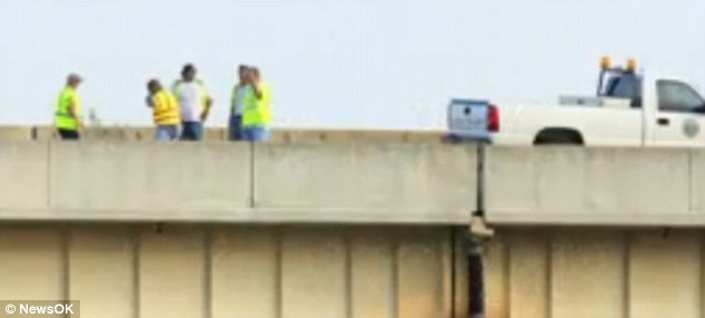 Danger on the roads: Emergency workers on the  Belle Isle bridge in Oklahoma City on Monday after the heat caused an expansion joint to buckle