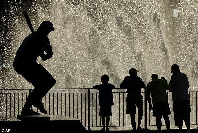Sweltering: Baseball fans stand in the mist of fountains during 100 degree weather at Kauffman Stadium before a baseball game between the Kansas City Royals and the Chicago White Sox