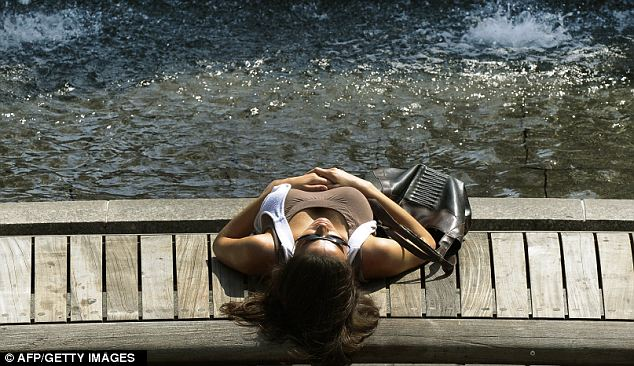 Cool down: Heather White of New York lays down next to the fountains at Columbus Circle