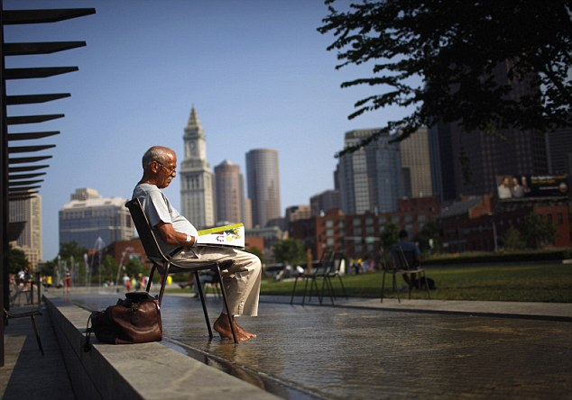 Respite: A man soaks his feet in a fountain while reading a magazine on the Rose Kennedy Greenway on a warm summer afternoon