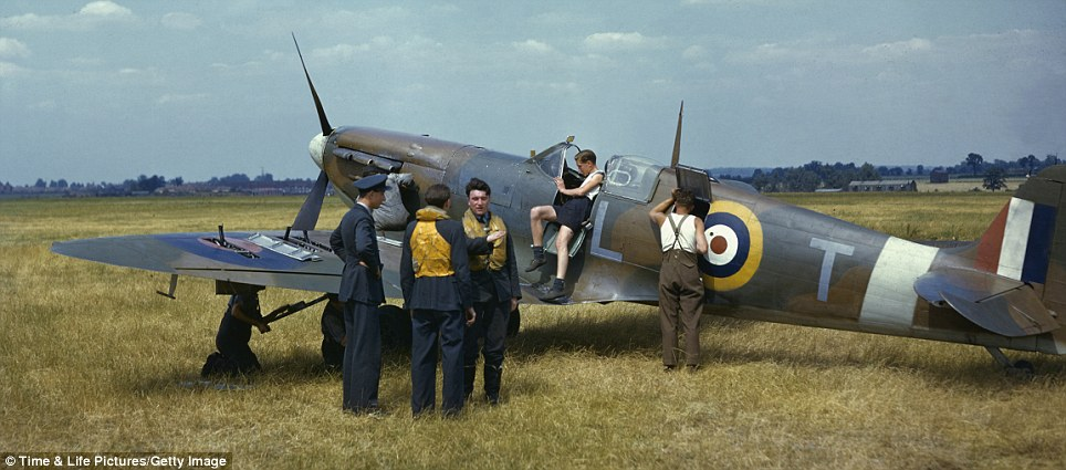 Preparing for battle: As ground crewmen inspect a Supermarine Spitfire fighter plane in a deserted field outside of London in 1941 pilots discuss their strategy for fighting in the air