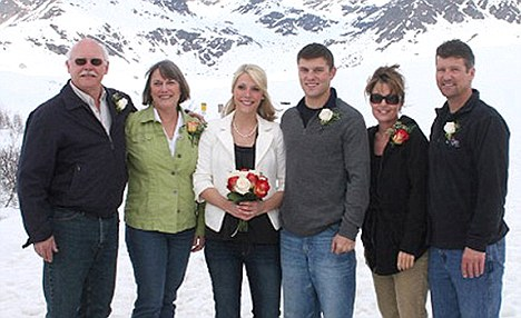 Newlyweds: Britta Hanson and Track Palin, surrounded by their parents - including Sarah Palin (R), after exchanging vows on a ski slope in May