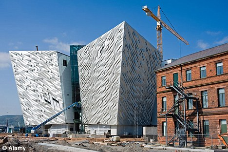 The futuristic new Titanic Museum is pictured under construction in Belfast with the original Titanic drawing office on its right