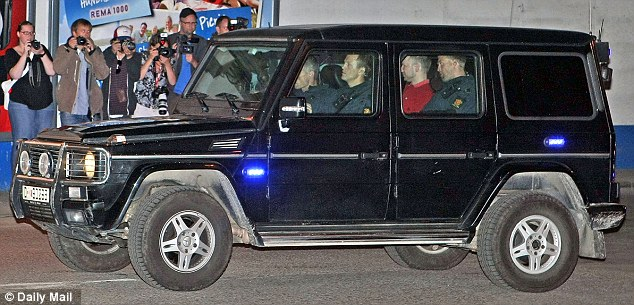 Police presence: Breivik was escorted by a number of officers as he was driven to the courthouse
