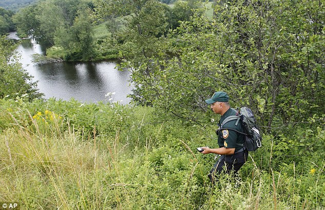 Hunt: A New Hampshire Fish and Game officer uses as GPS device as he searches for Celina along a road near her home in Stewartstown. An FBI abduction team has now joined the investigation