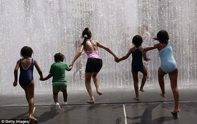 Cool down: A group of children run into a fountain on the South Bank in London as temperatures hit 82f (or 28c)