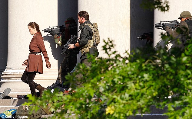 Heavy duty: She was seen surrounded by machinegun-toting  soldiers in the scenes filmed at the Mellon Institute building in Oakland, Pittsburgh