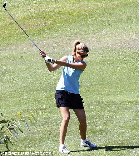 Taking a shot: A focused Delta practices her perfect swing at the course