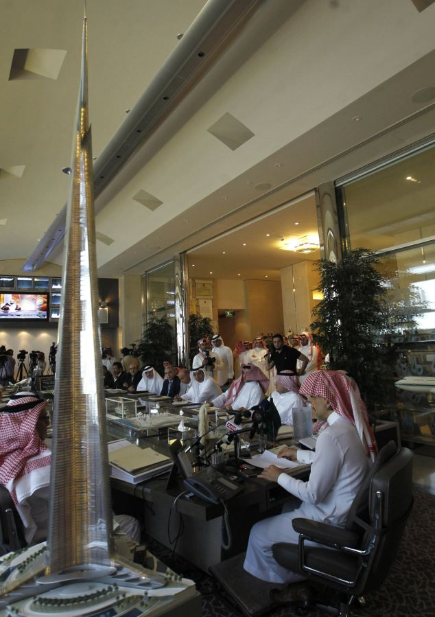 A model of the world's tallest tower stands next to Prince Alwaleed bin Talal as he speaks at a meeting