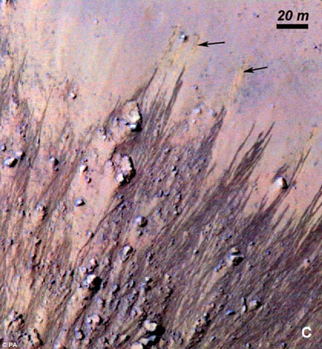 Signs of water? The finger-like features visible in images from Mars may be streams of salty water spilling over the rims of craters, scientists believe