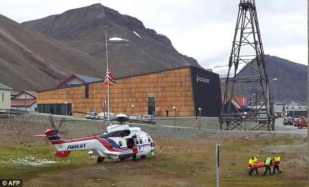 Attack: One of the victims of the polar bear attack is carried from a helicopter in Longyearbyen yesterday