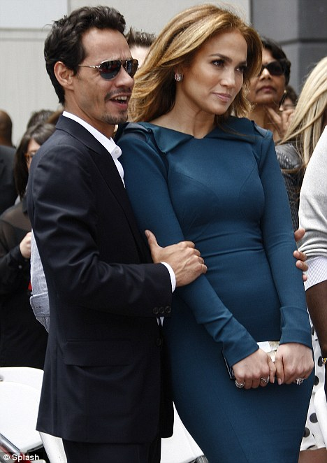 Body language reveals all: Jennifer seemed to be pulling away from her hubby back in May as he clung to her arm at Simon Fuller's star ceremony