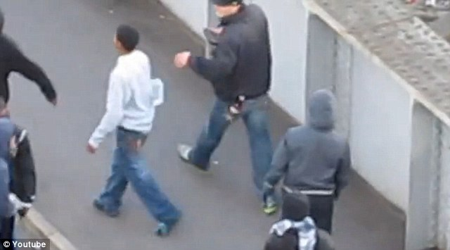 The robber, having taken the items from the teen's bag, then casually throws them to the floor before strolling away