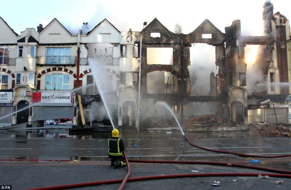 Aftermath: A fire fighter douses a burnt out building in Croydon, Surrey, following a third night of civil unrest on the streets of London