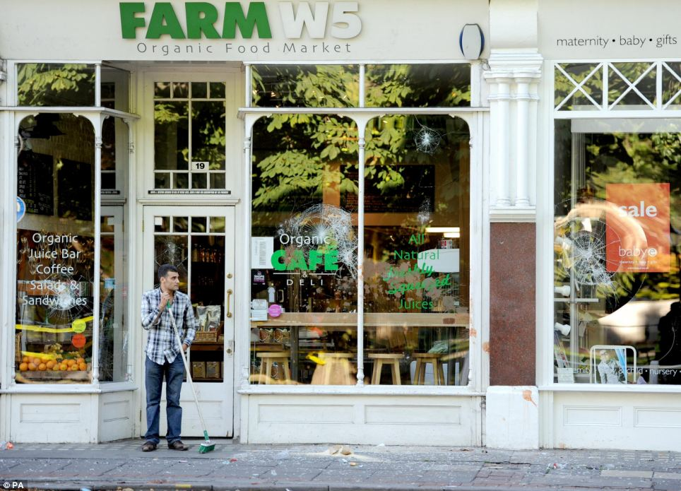 A man sweeps glass from outside an organic food shop on Ealing High Street