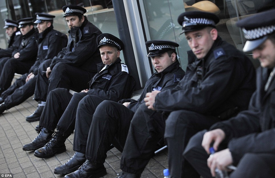 Ready and waiting: This group of Metropolitan Police sit outside a shop in Wandsworth, South West London, part of 16,000 officers on duty in the capital last night to quell the riots