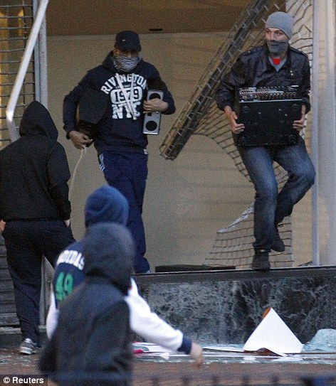 Looters carry equipment out of a home cinema shop in central Birmingham