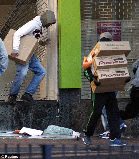 Looters carry boxes out of a home cinema shop in central Birmingham