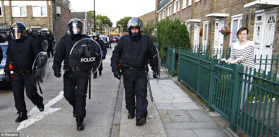 On patrol: A group of riot police walk through an East London estate yesterday