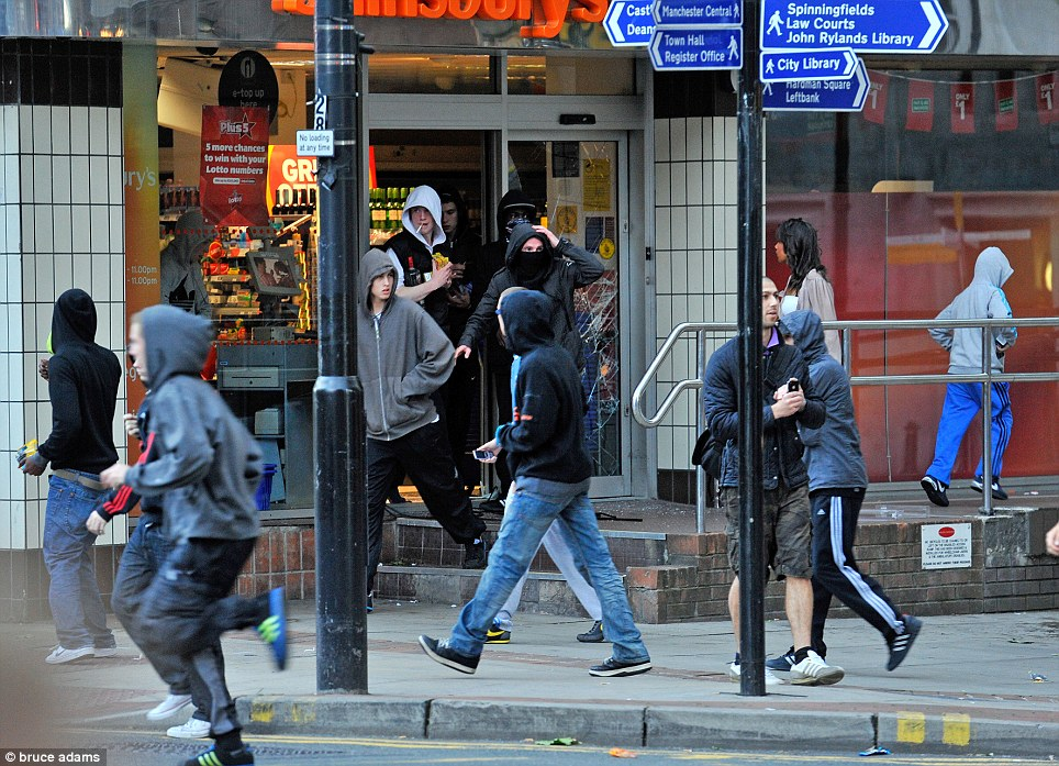 Free for all: Youths spill out of the damaged store in Manchester after filling their pockets with cigarettes and bottles of alcohol