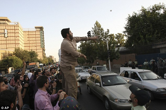 Missile: A demonstrator throws an egg at the fortified entrance of the Iranian embassy in Tehran