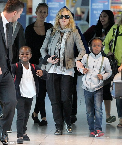 All the gang: Madonna jets into London from New York with Lourdes, David and Mercy in tow