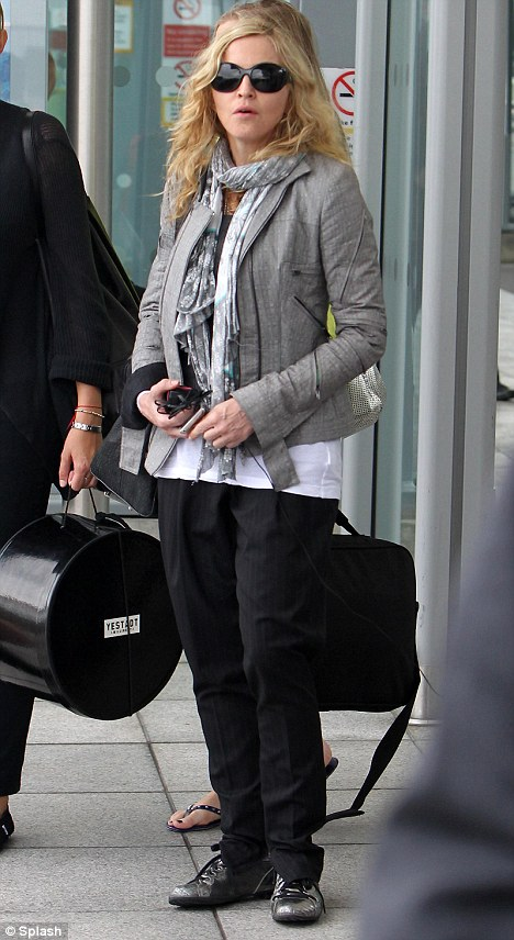 Where's my car? Madonna waits outside the terminal for her ride to her London home