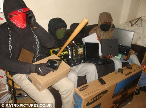 Thugs: A teenage gang display various electronic items they have looted during the recent riots in London