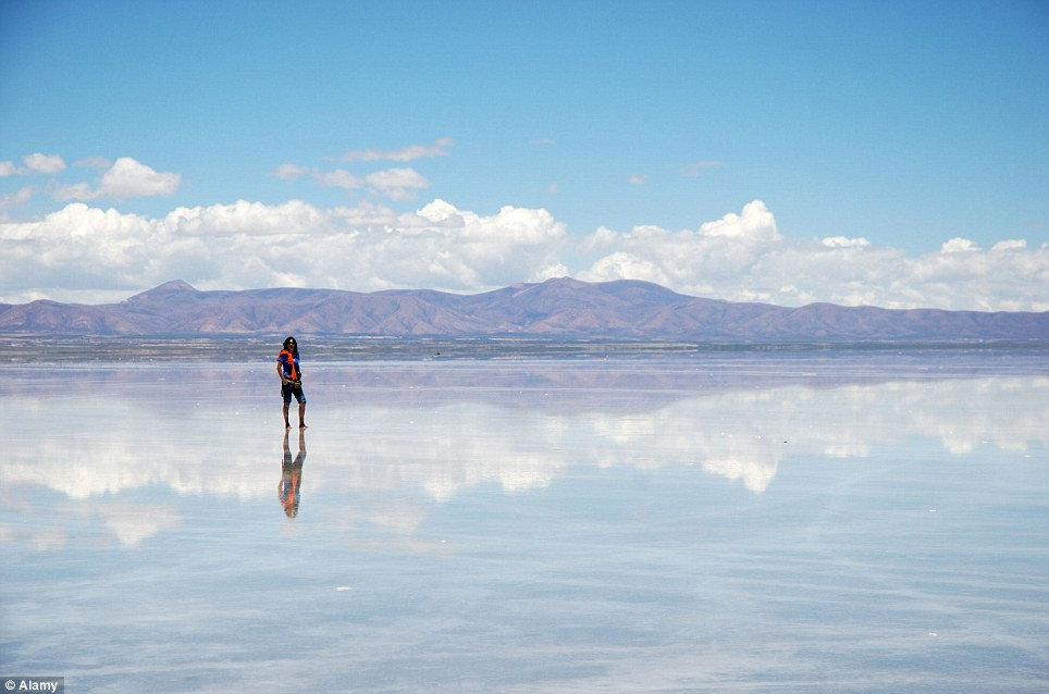 Mirror image: This tourist visiting the South American region is reflected in the salt flats, which are over 3,000m above sea level