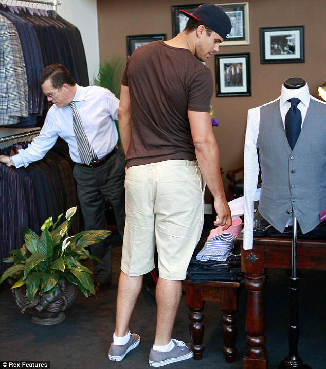 Not long now: The New Jersey Nets star waits in the shop as his wedding attire is put into suit bags