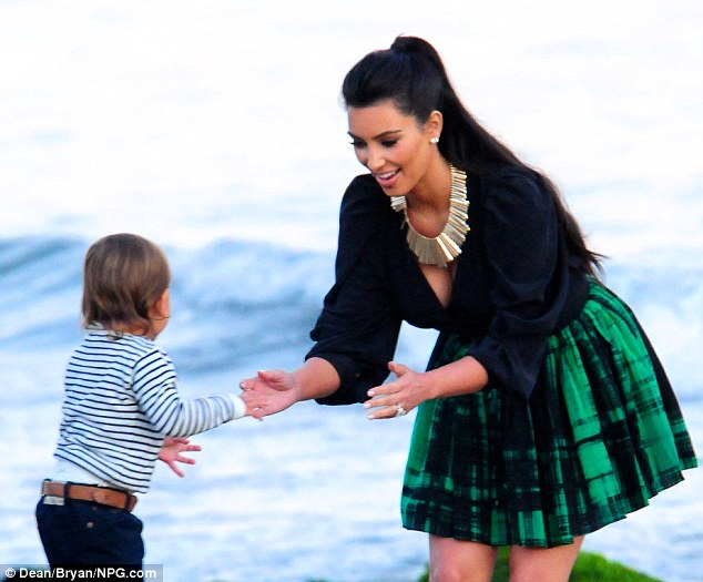 Play time: The doting aunt went barefoot on the beach as she walked the shore with her 18-month-old nephew Mason Disick