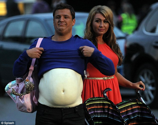 It's not real: Mark shows off his prosthetic belly inbetween takes