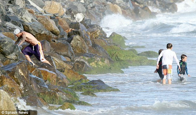 Windy weather: Becks clambers up the rocks while his three sons paddle in the water on the windy day