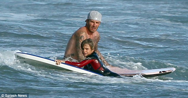 Surf's up: Beckham keeps a close eye on Romeo as he hangs out on the board