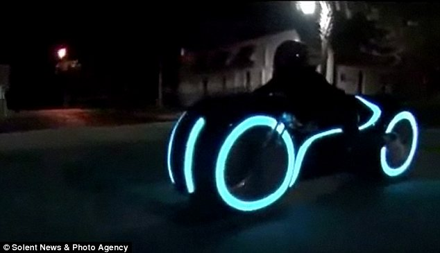 The bike is lit up with electroluminescent strips built into the tire cowlings, wheel rims and body