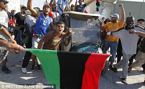 Joy: Libyan rebel fighters celebrate near a golf buggy belonging to Muammar Gaddafi at the entrance of Bab al Aziziya compound in Tripoli