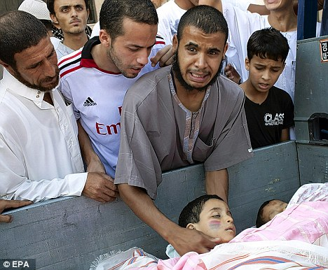 Human cost: Men mourn the death of two children killed by snipers in Tripoli during the battle between Gaddafi's troops and rebel fighters