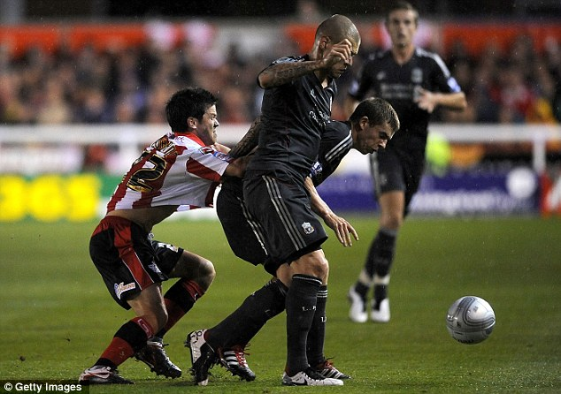 Squeezed out: Keohane of Exeter is patrolled by Liverpool's Skrtel and Flanagan