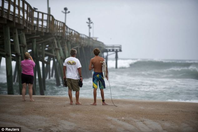 Waiting game: Beach goers watch the surf near a beachside fishing pier a day before the expected landfall of Hurricane Irene in Atlantic Beach, North Carolina
